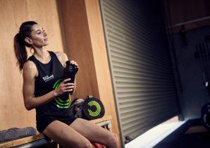 Kvinde drikker proteinshakes til vægttab efter træning