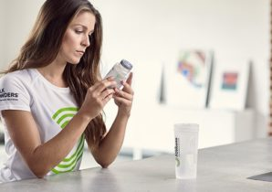 woman holding zinc tablets next to a shaker bottle